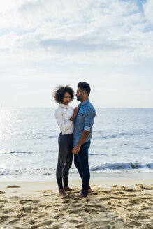 Spain, Barcelona, couple standing barefoot on the beach - BOYF01285
