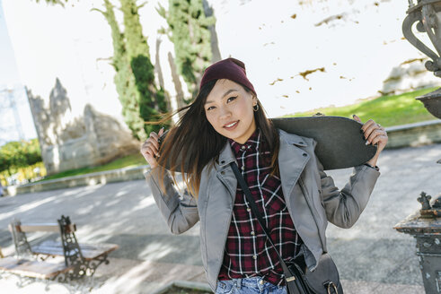 Portrait of smiling young woman with skateboard on her shoulders - KIJF02204