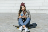 Smiling young woman sitting on her  skateboard looking at smartphone - KIJF02207