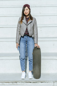 Portrait of young woman with skateboard and smartphone - KIJF02210