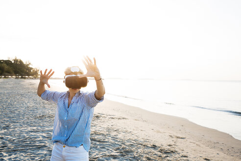 Thailand, Rayong, woman using Virtual Reality Glasses on the beach - HMEF00181