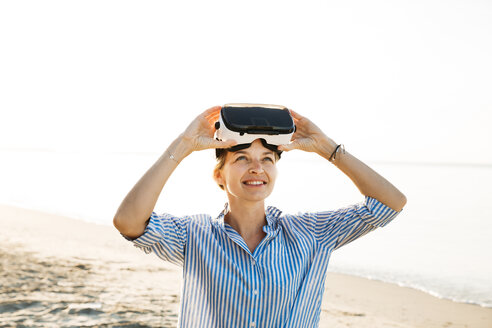 Portrait of smiling woman with Virtual Reality Glasses on the beach - HMEF00184