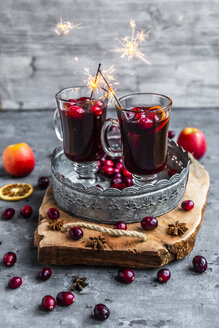 Two glasses of Mulled Wine with cranberries, orange slices and star anise with sparklers - SARF04058
