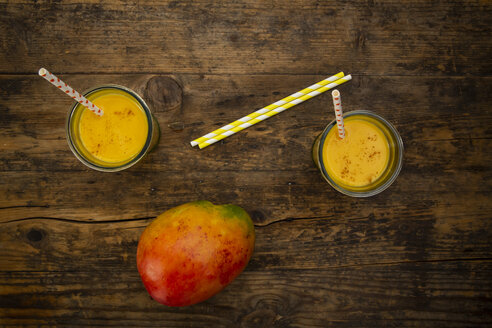 Mango and two glasses of Mango Lassi with curcuma and straws on wood - LVF07685