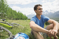 Man with mountain bike sitting in grass - HEROF07674