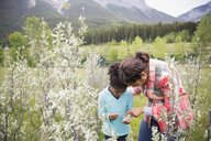 Mother and daughter looking at plant in field - HEROF07749