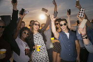 Friends with cell phones cheering at rooftop party - HEROF07752