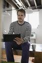 Portrait of businessman with digital tablet in office - HEROF07806