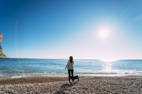 Spain, Alicante, Benitachell, back view of woman standing on the beach with her dog looking at view - OCMF00229