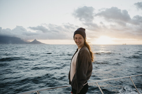 South Africa, young woman with woolly hat smiling during boat trip at sunset - LHPF00390