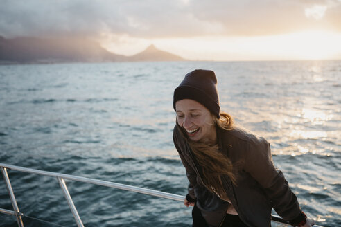 South Africa, young woman with woolly hat during boat trip at sunset - LHPF00396