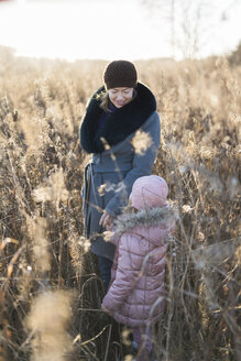 Little girl standing hand in hand with her mother on autumnal meadow at Golden hour - PSIF00223