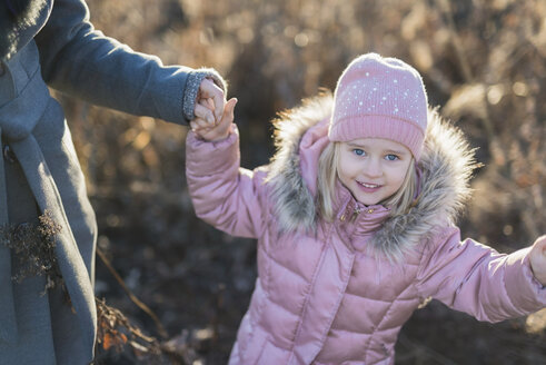 Portrait of little girl hand in hand with her mother on autumnal meadow at Golden hour - PSIF00226