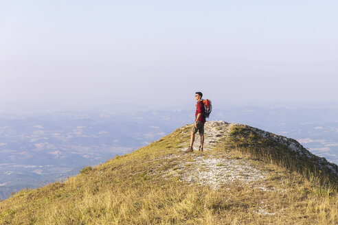 Italy, Monte Nerone, hiker on top of a mountain looking at panorama - WPEF01297