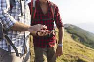 Italy, Monte Nerone, close-up of two men hiking and using smartphone in mountains - WPEF01300