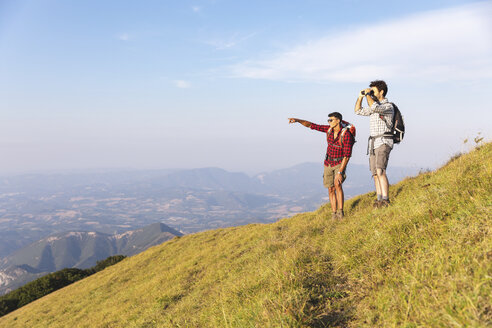 Italy, Monte Nerone (PU), two hikers on top of a mountain enjoying the view - WPEF01306