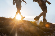 Italy, Monte Nerone, close-up of two men hiking in mountains at sunset - WPEF01309