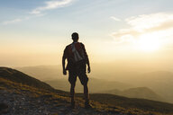 Italy, Monte Nerone, hiker on top of a mountain looking at panorama at sunset - WPEF01315