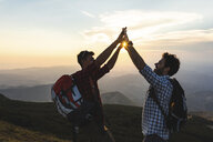 Italy, Monte Nerone, two happy and successful hikers in the mountains at sunset - WPEF01318