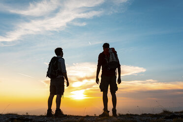 Italy, Monte Nerone, two hikers enjoying the view on top of a mountain at sunset - WPEF01321