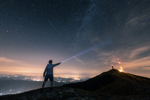 Italy, Monte Nerone, silhouette of a man with torch under night sky with stars and milky way - WPEF01324