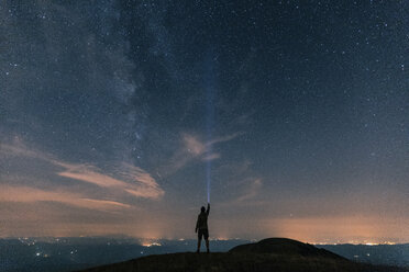 Italy, Monte Nerone, silhouette of a man with torch under night sky with stars and milky way - WPEF01327
