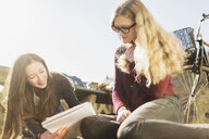 Teenage friends reading book while sitting in college campus - ASTF02677