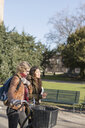 Teenage friends with bicycle walking on footpath in college campus - ASTF02689
