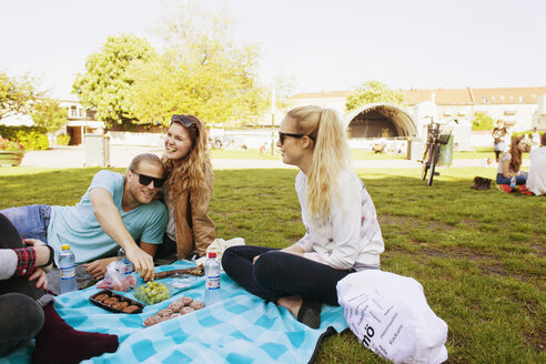 Happy friends enjoying picnic at park - ASTF02695