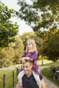 Happy man carrying daughter on shoulders while walking at park - ASTF02737
