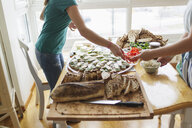 Midsection of woman passing bowl to friend while preparing open faced sandwich at home - ASTF02761