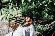 Young woman wearing hat while sitting on chair in park - ASTF02785