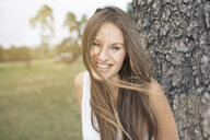 Portrait of laughing young woman leaning against tree trunk - PNEF01179