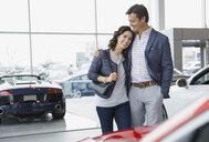 Couple hugging in car dealership showroom - HEROF07873