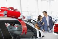 Couple hugging in car dealership showroom - HEROF07882