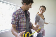 Couple measuring room with tape measure - HEROF07888