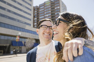 Couple laughing on sunny urban street - HEROF07900