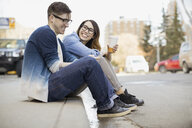 Hipster couple drinking coffee on urban curb - HEROF07909