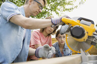 Father teaching children to use table saw - HEROF07921