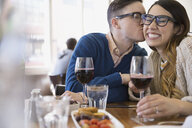 Couple with wine kissing in bistro - HEROF07954