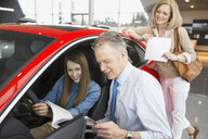 Family looking at car in car dealership showroom - HEROF07984