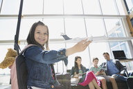 Girl playing with toy airplane in airport - HEROF07999