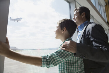 Father and son at sunny airport window - HEROF08005