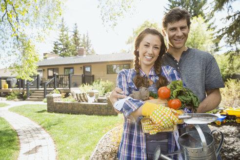 Couple holding freshly harvested vegetables - HEROF08038