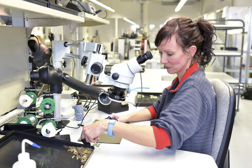 Woman working on quality control in the manufacturing of circuit boards for the electronics industry - LYF00877