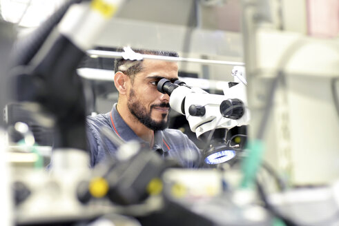 Man using a microscope for the quality control in the manufacturing of circuit boards for the electronics industry - LYF00886
