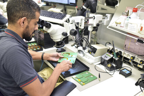 Man using a microscope for the quality control in the manufacturing of circuit boards for the electronics industry - LYF00889