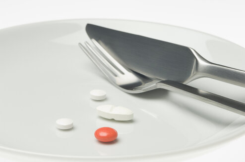 Pills on a plate with cutlery - CRF02812