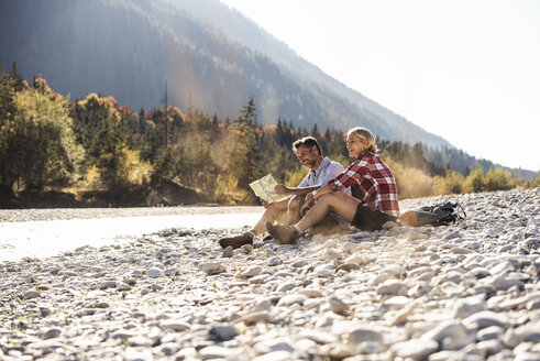Austria, Alps, couple on a hiking trip having a break at a brook reading map - UUF16520