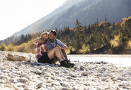 Austria, Alps, affectionate couple on a hiking trip having a break at a brook - UUF16523